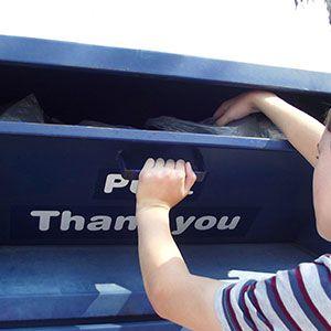 Boy donating clothes into a clothing bin