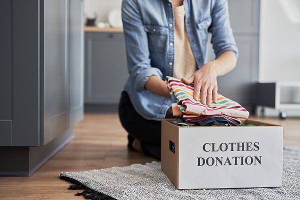 Woman putting her clothes in a donation box