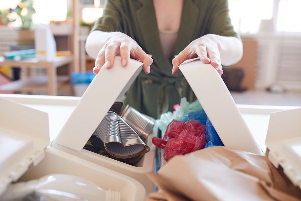 Young woman sorting homewares for donation to charity
